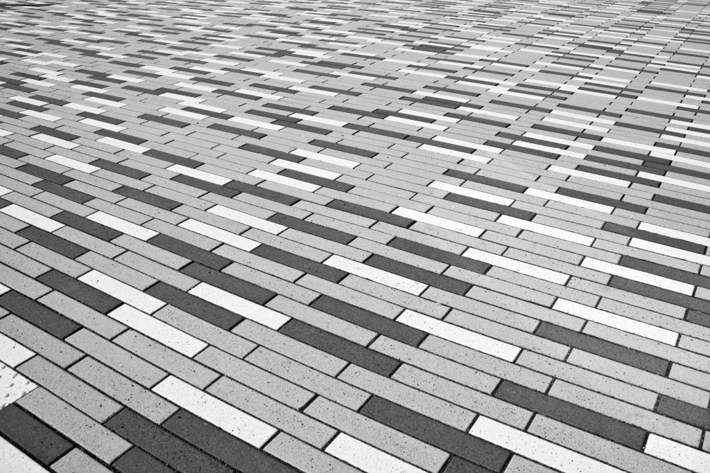 Driveway designed with interlocking stone in long, linear patterns varying in shades of grey.