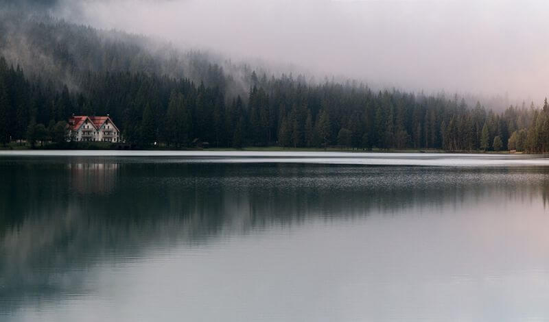 A beautiful cottage sits on the edge of a wooded hillside, seen from across a foggy lake on a misty day.