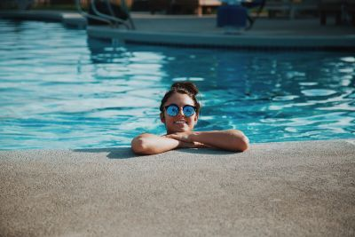 Smiling girl wearing sunglasses is inside a swimming pool leaning against the side.