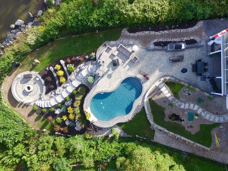 aerial view of beautifully landscaped back yard with stone work and inground pool