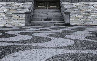 View of the entrance of a home designed entirely of interlocking stone in various colours and patterns