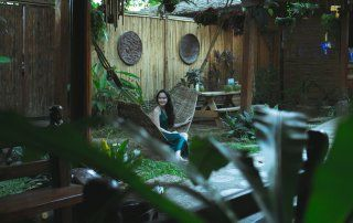 A woman sits in a hammock in a lush, green backyard with a stone patio.