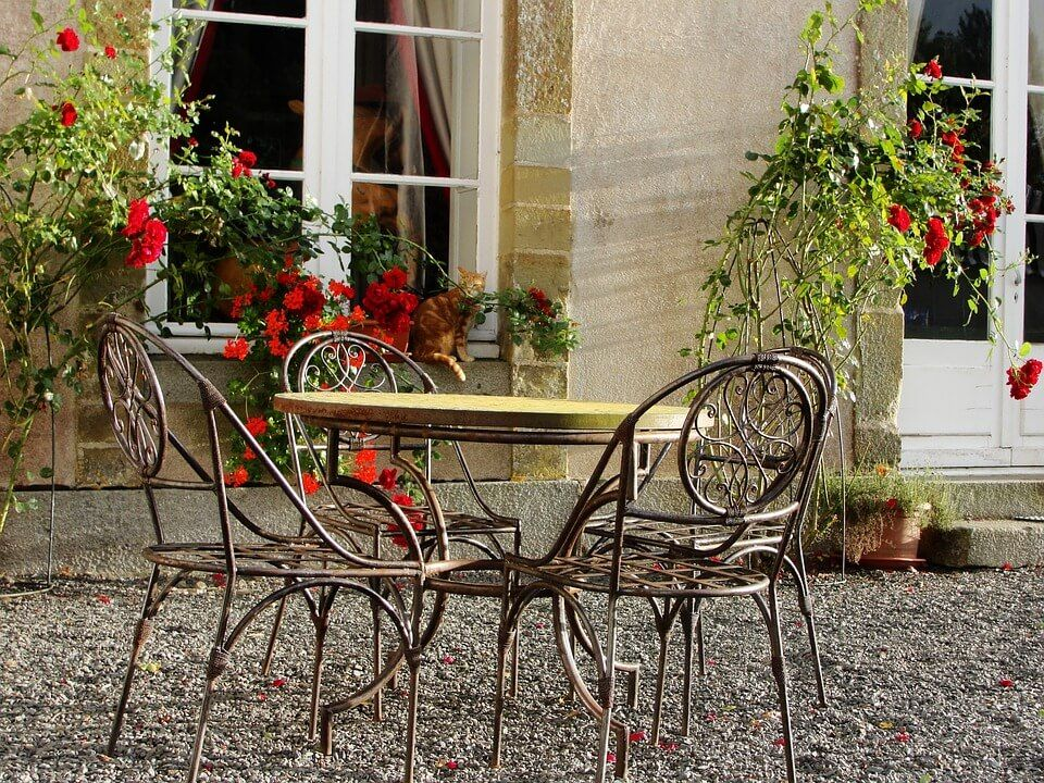 Wrought iron chairs sit around a patio table next to a building.