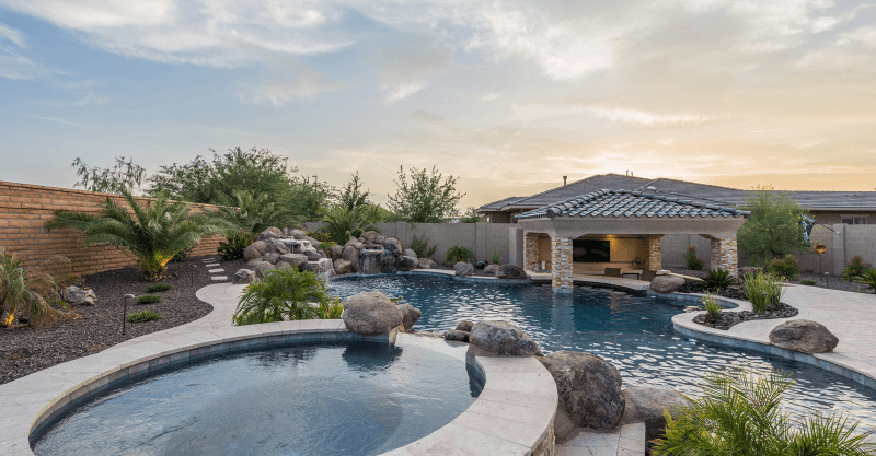 Landscape of a home with pool and spa with decorative boulders