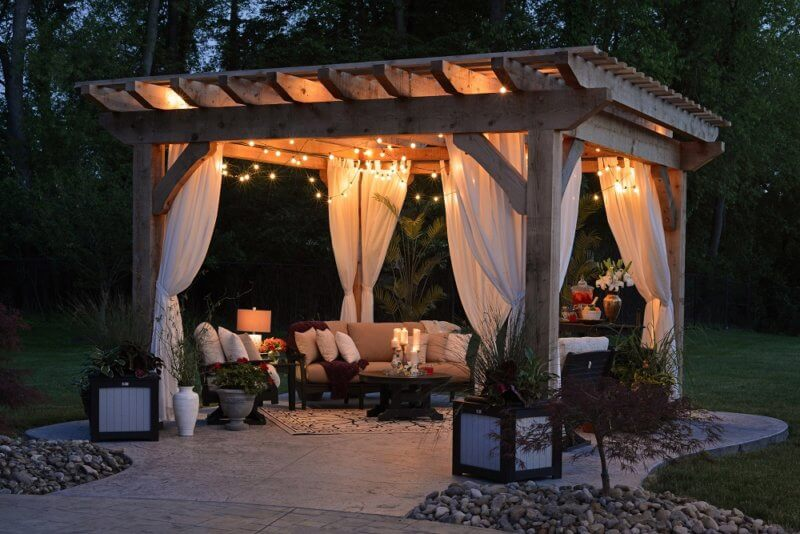 Backyard gazebo set up at night with lights and beautiful patio furniture on a manicured lawn