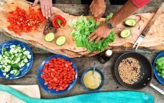People chopping vegetables in outdoor kitchen