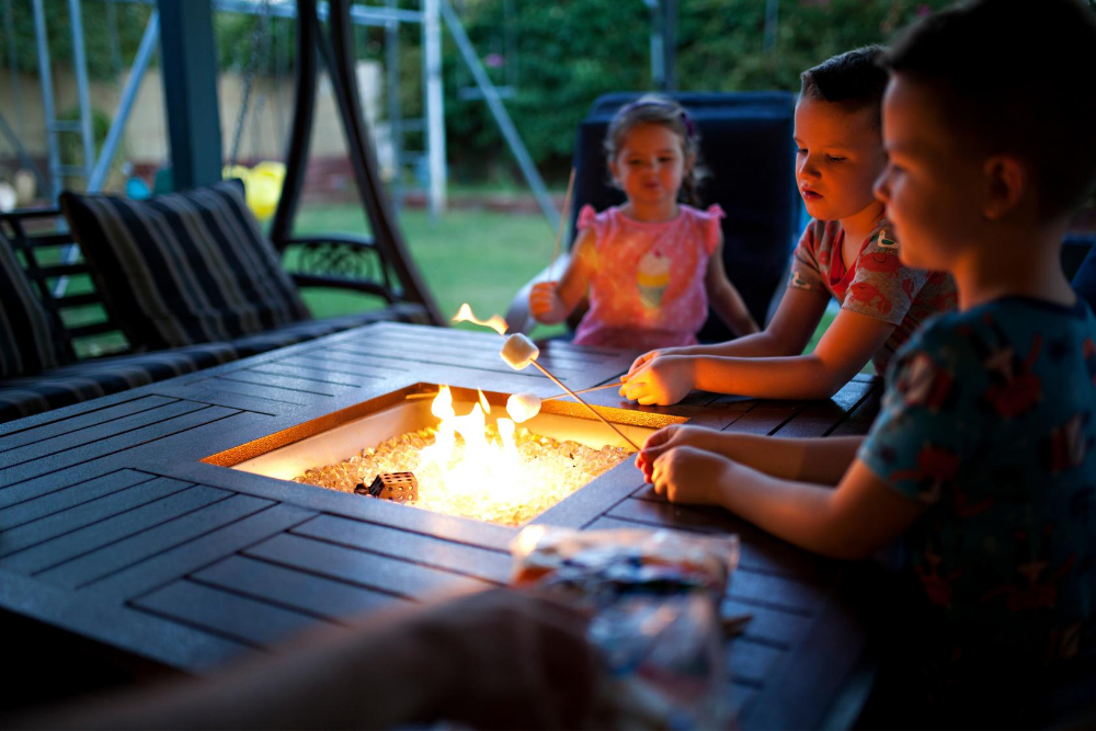 children roast marshmallows over a fire pit in their backyard