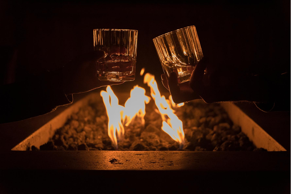 two people cheers their whiskey glasses over an outdoor fire pit