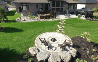 aerial view of low-maintenance backyard landscaping with firepit and interlocking stone