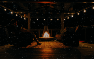 man enjoying his patio at night in the snowfall