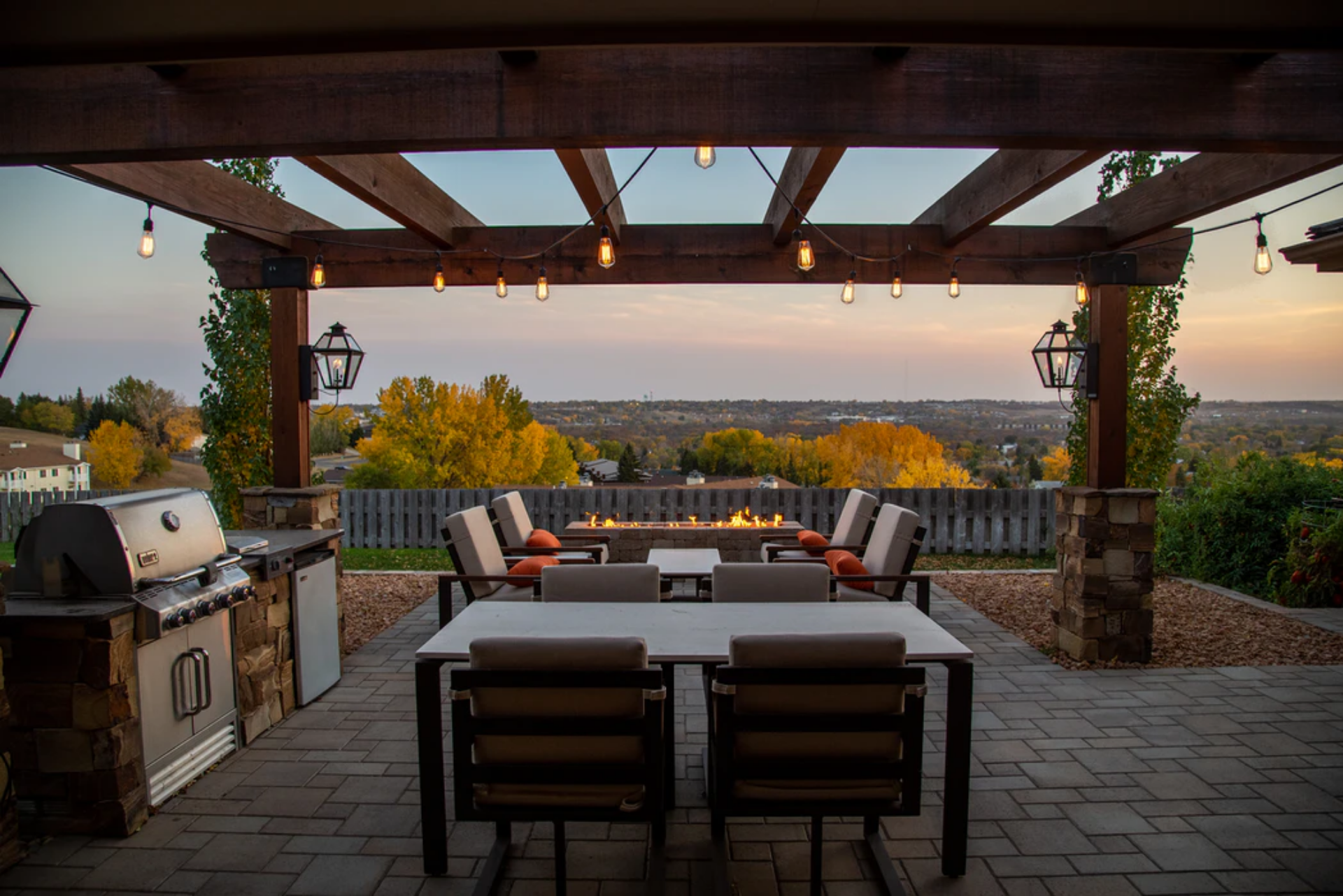 view of backyard home landscape under pergola with outdoor kitchen and dinning area